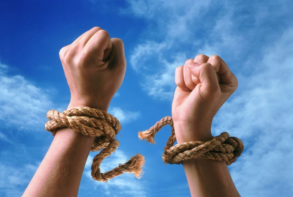 a pair of hands breaking free from a rope tied around their wrists with the blue sky in the background