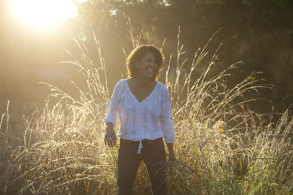 a woman is laughing as she stands in a field of tall grass. the sun rises behind her causing a halo effect on her and the grass.